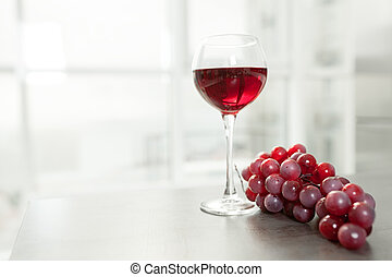 A glass of red wine stands on a table next to a bunch of red grapes. White kitchen with a large panoramic window on the background