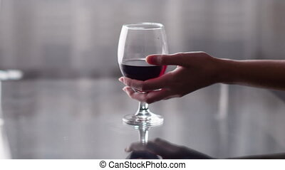 A glass of red wine stands on the table, a woman's hand takes a glass
