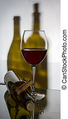 A glass of red wine with a corkscrew and a bottle