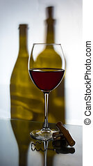 A glass of red wine with a corkscrew on the background of two wine bottles
