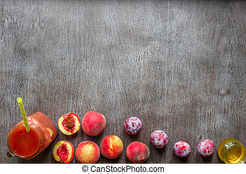 A glass of smoothies made of peach and plums on a wooden background