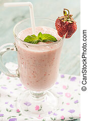 A glass of strawberry milk shake with fresh strawberries and mint.