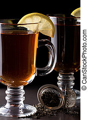 A glass of tea with a strainer on a dark background