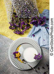 A glass of vanilla smoothie on a round plate. Blue and yellow fabric with purple flowers. A white milkshake on a gray background.