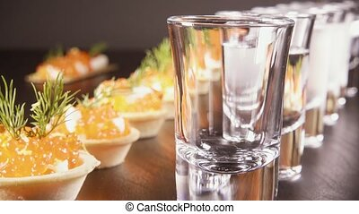 A glass of vodka on the table with a snack