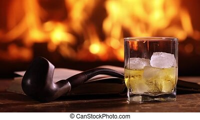A glass of whisky, an open book, and a pipe on the table. -...