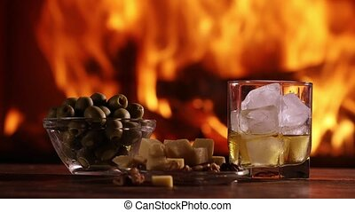 A glass of whisky and plate with cheese, olives and nuts are...