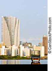 A glass of whisky with city view on background
