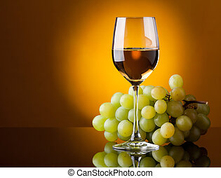 A glass of white wine and a bunch of green grapes on a...