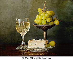 A glass of white wine, soft cheese and grapes