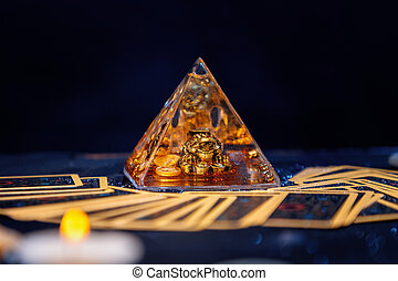 A glass pyramid with a Golden frog. Tarot cards are scattered on the table. Close-up. Copy space. The concept of divination, magic and esotericism