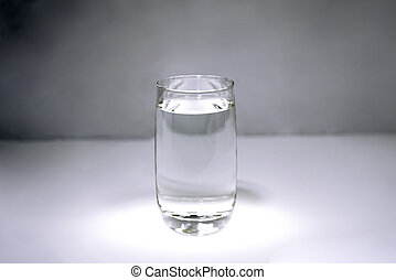 A glass with clear water on gray background.