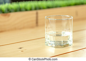 a glass with half water in it, on the wood table and green grass background.