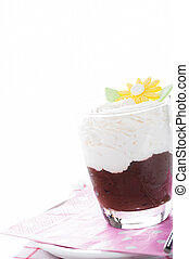 A glass with mousse au chocolat and whipped cream on white...