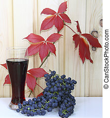 A glass with wine and grapes against red leaves and a wooden wal