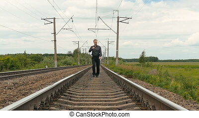 A gloomy person walks along the railway tracks. Problems,...