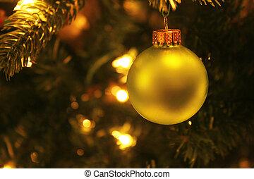 Gold Christmas tree ornament on lit tree