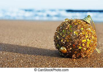 christmas ball on the sand of a beach
