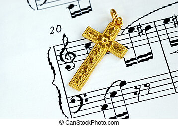 A golden cross on the top of a music sheet