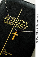 A golden cross on the top of  the bible