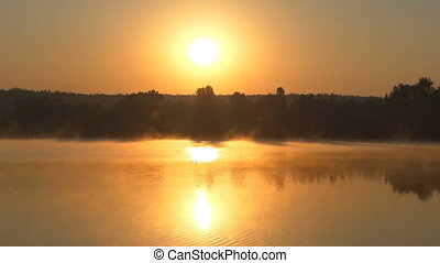 A golden lake with a blurring haze and green banks looks...
