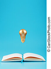 A Golden light bulb in levitation from an open notebook on a blue background. Concept of the idea.