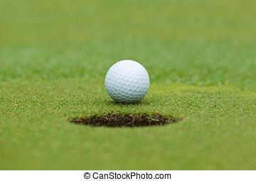 A golf ball and hole