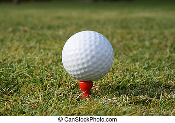 A golf ball on a red tee waiting to be hit.