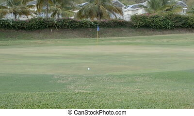 A golf ball rolling close to the hole