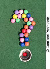 A number of gaily colored golf balls formed into the shape of a question mark, using the silver cup as the period marker.