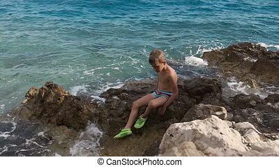 A good little boy sits on a rock and looks at the roaring sea. Dalmatia. Croatia