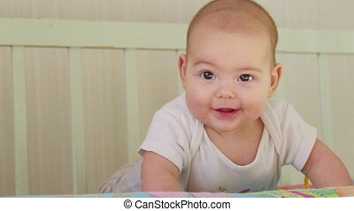 A gorgeous little baby smiles at the camera with a nice soft focus background
