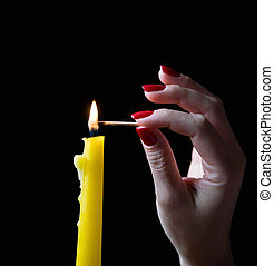 A graceful female hand with a beautiful manicure lights a candle.