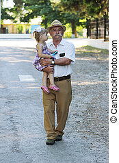 grandfather with his granddaughter are on the road - a...