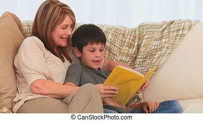 A grandmother reading a book to her grandson