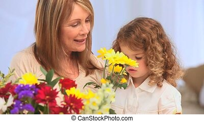 A grandmother with her grand daughter making a bunch of flowers