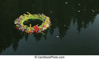 A grass and flower wreath floating on the water. Ethnic decor. Slavic tradition. Ivana Kupala pegan holiday