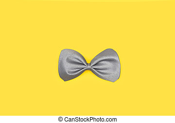 A gray bow tie on a yellow background