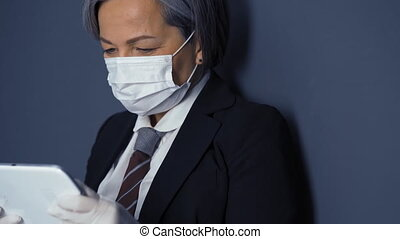A gray-haired business woman in a protective mask holds a ...