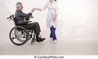 A Gray Haired Man in a Wheelchair is Dancing with a Asian Looking Nurse.