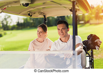 A great day for golf. A couple is sitting in a white golf cart. On the trunk lies a bag with golf clubs