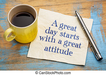 A great day starts with a good attitude - handwriting on a napkin with a cup of espresso coffee