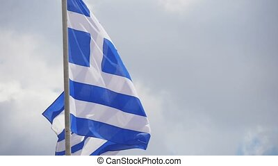 A Greek flag with a cross and stripes fluttering solemnly on...