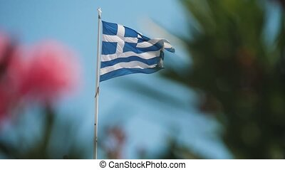 A Greek flag with stripes and a cross flying solemnly in celeste sky in slo-mo