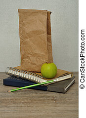 A green apple. a paper lunch bag and a stack of books on a table with a white background