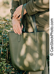 a green bag in the hands