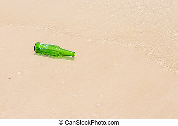 A green bottle of water on beach