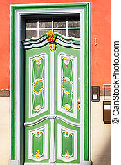 Green door on a red house