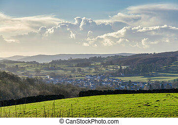 A green field with a village beyond and gowing cumulous...