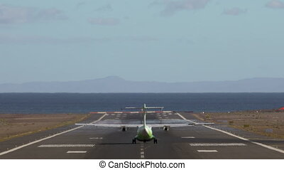 A long ride of a plane along a runway and its final take off, we see its green tail